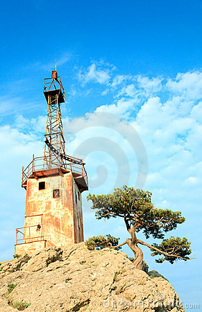 Old lighthouse on rock top on sky background