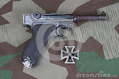 Luger Parabellum handgun and medal Iron Cross on camouflaged background