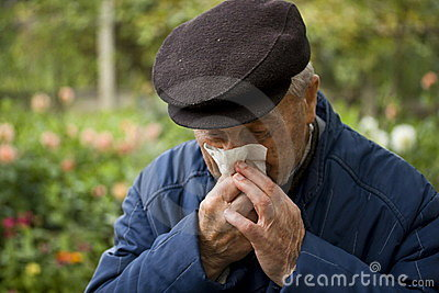 Old man blowing his nose