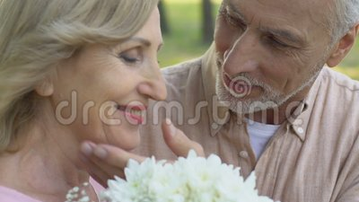 Old man bringing bouquet of flowers to woman and hugging her tenderly with love. Stock footage stock video footage
