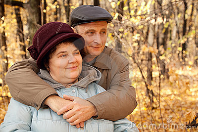 Old man embrace old woman in autumnal forest