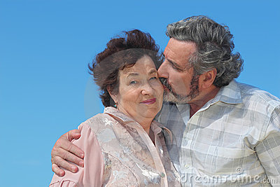 Old man embracing woman and kissing her cheek Stock Photo