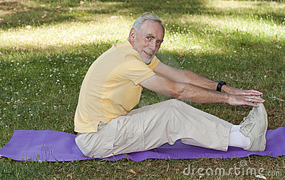 Old man exercising on mat in park