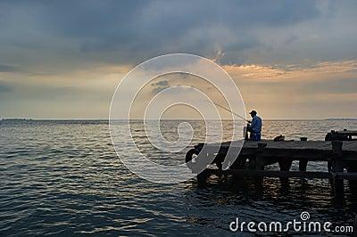 Old man fishing at the dock