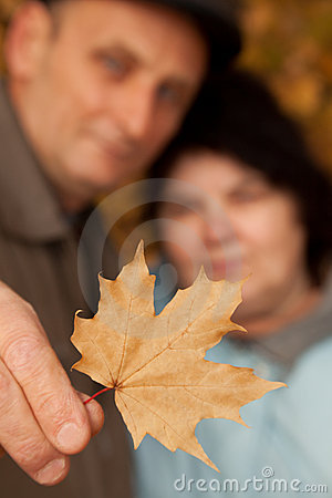Old man hold maple leave and embrace old woman