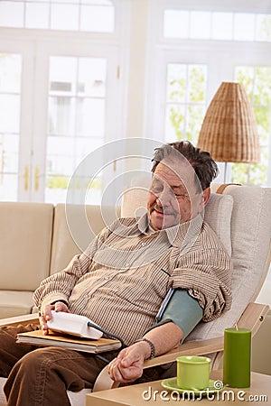 Old man measuring blood pressure at home