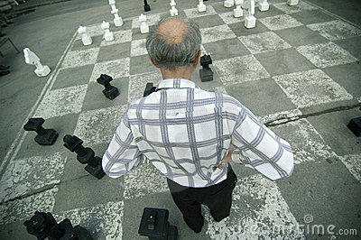 Old Man Playing Oversize Chess Board