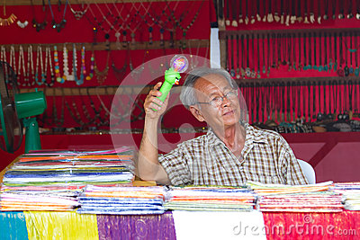 Old man selling souvenirs on the market in Thailand Editorial Stock Image