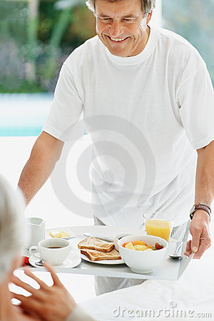 Old man serving a woman with healthy breakfast