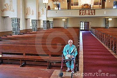 Elderly man sitting in an empty church