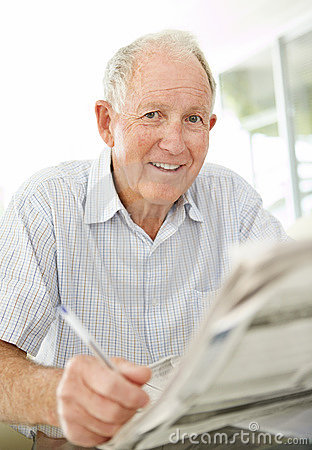 Old man solving crosswords in the newspaper