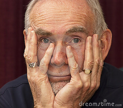 Old man staring into space with chin in hands