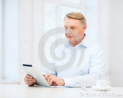 Old man with tablet pc computer at home