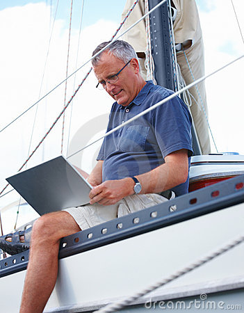 Old man using laptop while sitting at the edge of