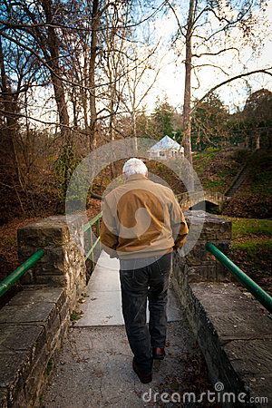 Free Old Man Walking Across A Bridge Outside Royalty Free Stock Photo - 28039555