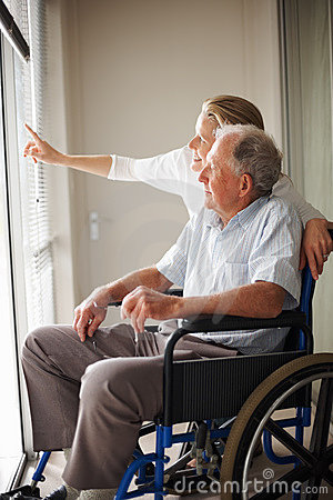 Old man on a wheelchair , nurse pointing outside
