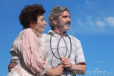 Old man and woman holding badminton rackets