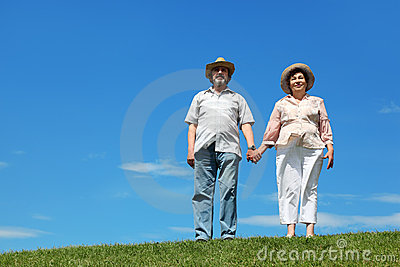 Old man and woman in straw hats standing on hill