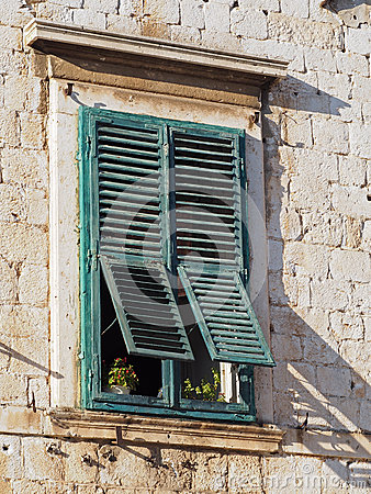 Old mediterranean window with green shutters