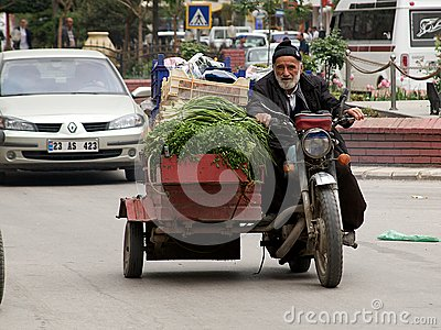 Old meets new on the streets of Turkish city. Grocer transporting his vegetables to bazaar market. Editorial Stock Photo