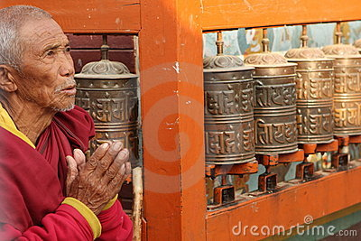Old monk reads mantra near praying mills Editorial Stock Photo