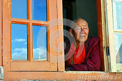 Old monk at the window in Ladakh (India) Editorial Stock Photo