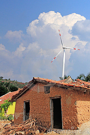 Old mud house in rural india with wind mill