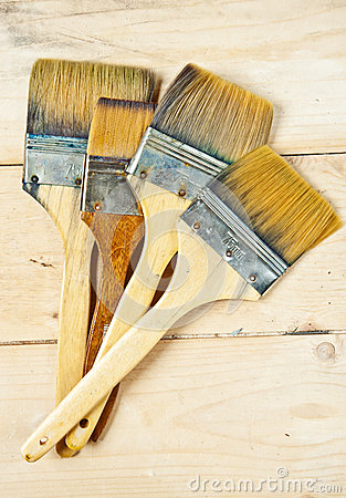Old paint brushes on wooden background