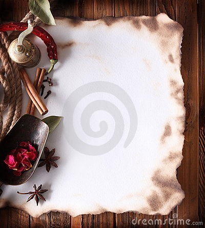 Old paper with spices on a wooden surface