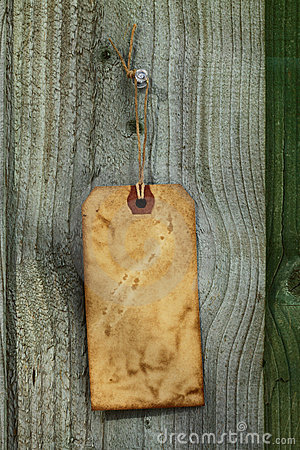 Old paper tag with string on wooden fence