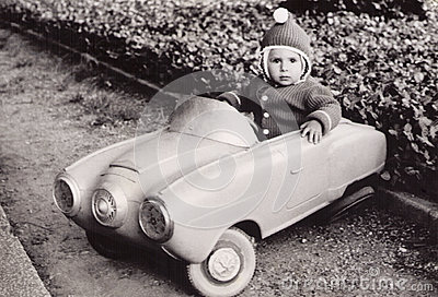 Old Photography of a little girl in a toy car