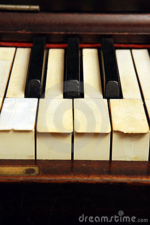 Old piano with ivory keys broken and scratched