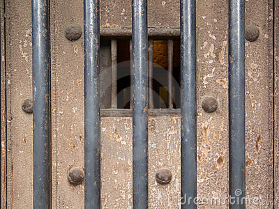 Old prison door with metal bars and window