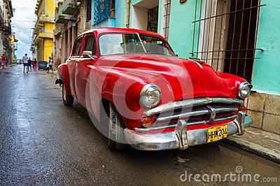 Old red car in a shabby street in Havana Editorial Photo