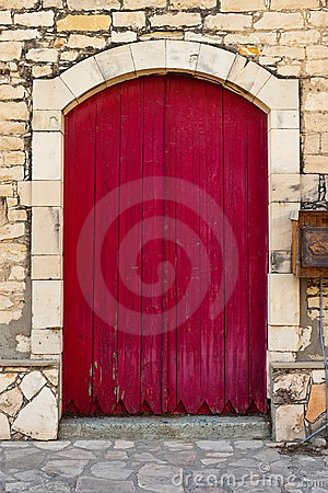 Old red door against an old stone wall