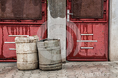 Old red doors with garbage baskets