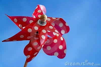 Old red toy windmill with white dots on blue sky