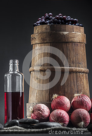 Old wine bottle with grapes,barrel and onions