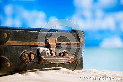 Old retro antique suitcase on beach
