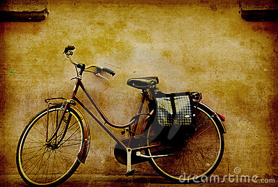Old retro bicycle against a grungy wall in italy