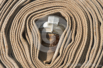 Old rolled fire hose with nozzle