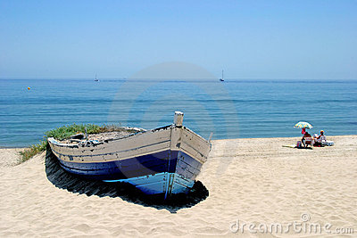 Old rowing boat on sunny white sandy beach