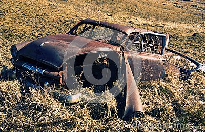 Old rusty abandoned car in a field