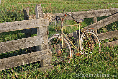 Old rusty bicycle against a fence in Holland