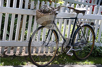 Old rusty bike leaned to the white fence