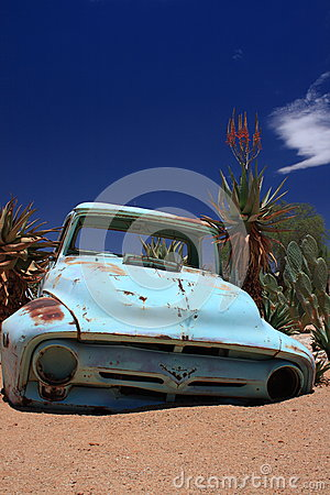 Old rusty car wreck stranded in desert