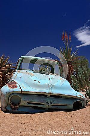 Old rusty car wreck stranded in desert