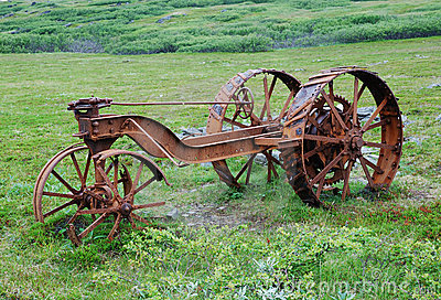 Old rusty machine in the green meadow