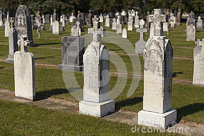 An old section of a small town graveyard during daylight. Editorial Stock Image
