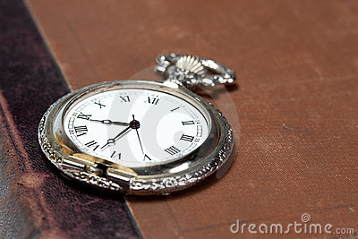 Old silver watch on the vintage book